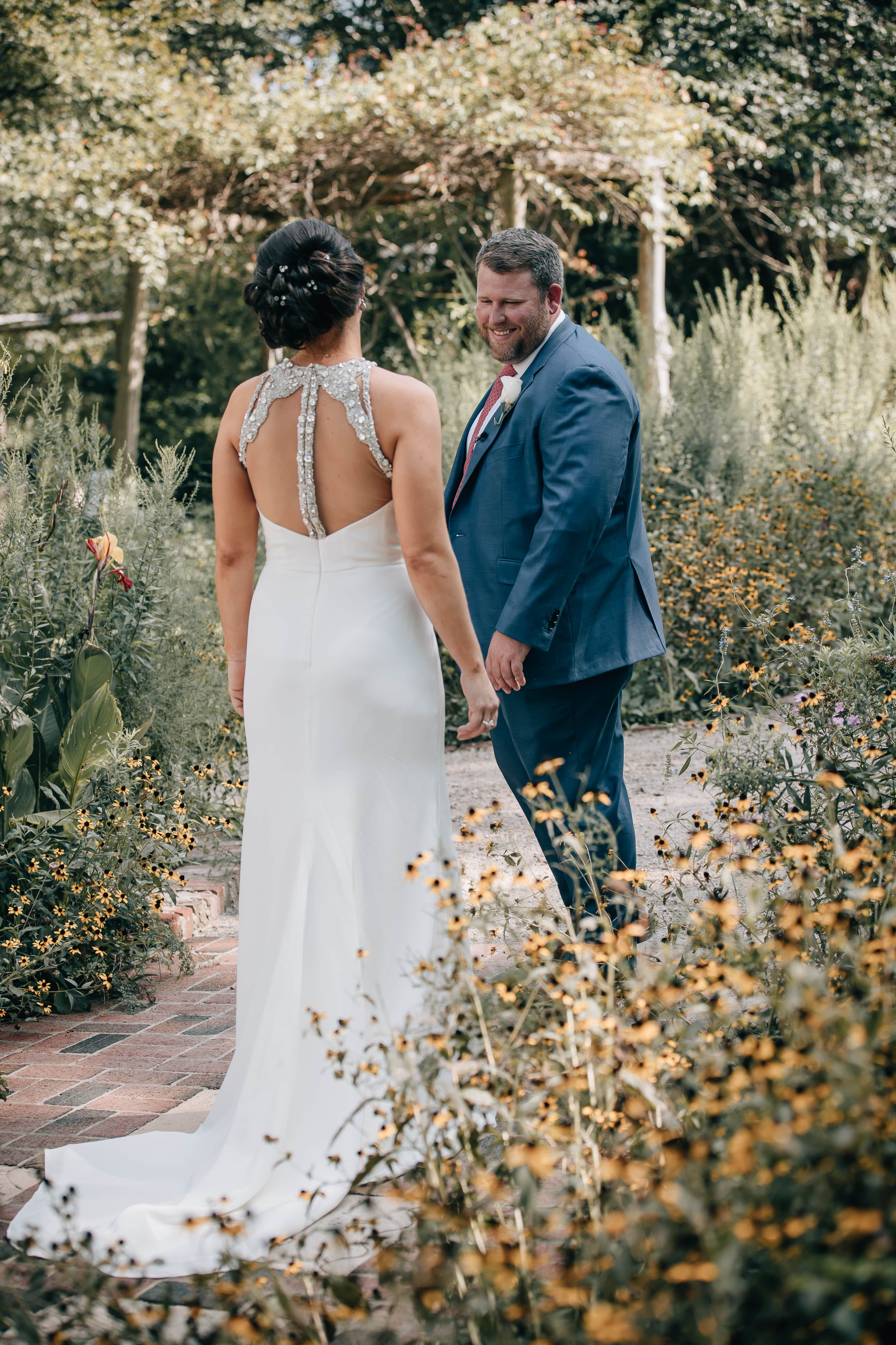 Groom sees is bride for the first time among the gardens of The Ivy Place captured by Shutter Owl Photography