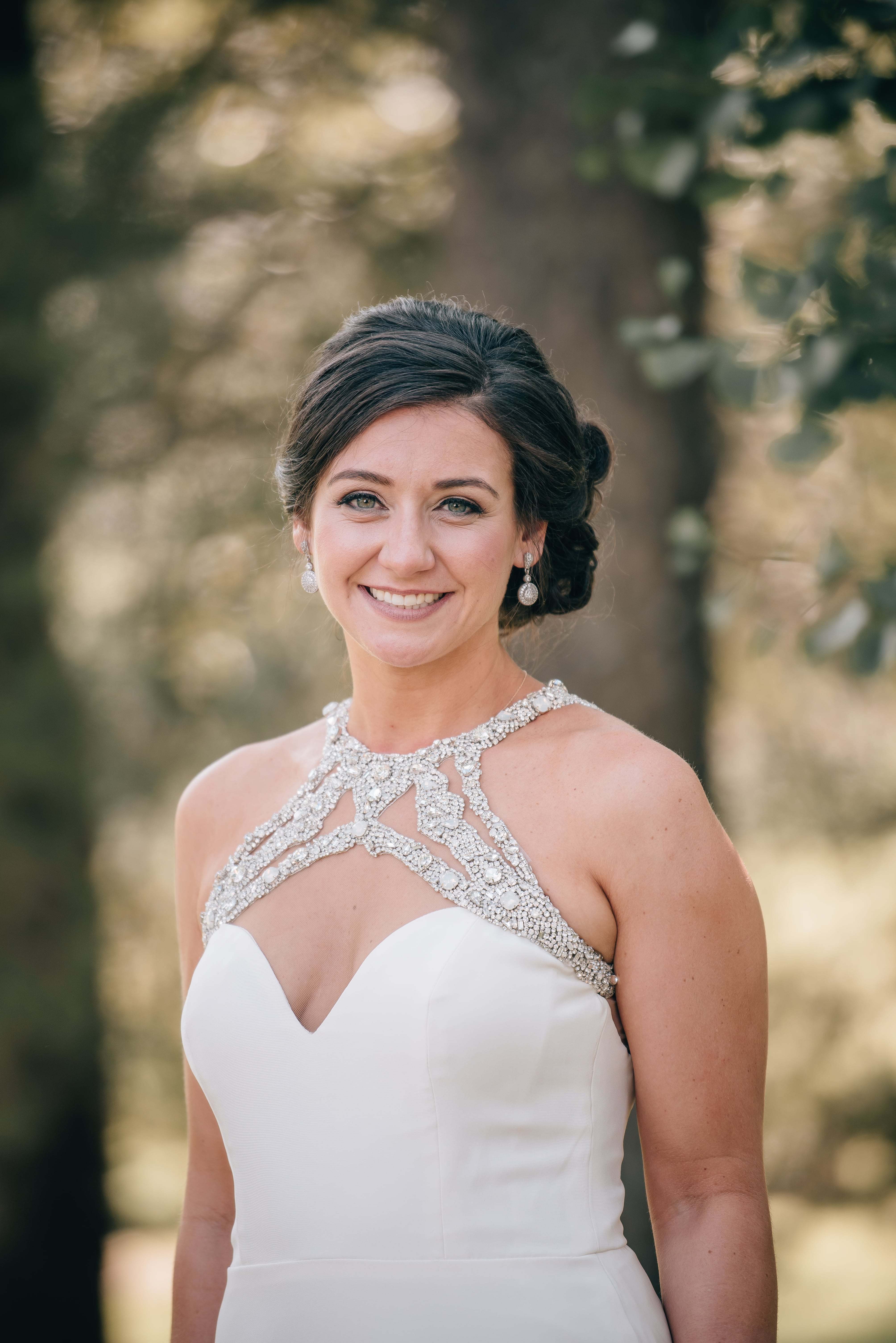 Bride has knotted updo and romantic makeup by Cali Stott Artistry for her summer wedding at The Ivy Place designed by Magnificent Moments Weddings