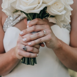 Bride holds a white rose bouquet made by Party Blooms for her summer wedding at The Ivy Pace captured by Shutter Owl Photography