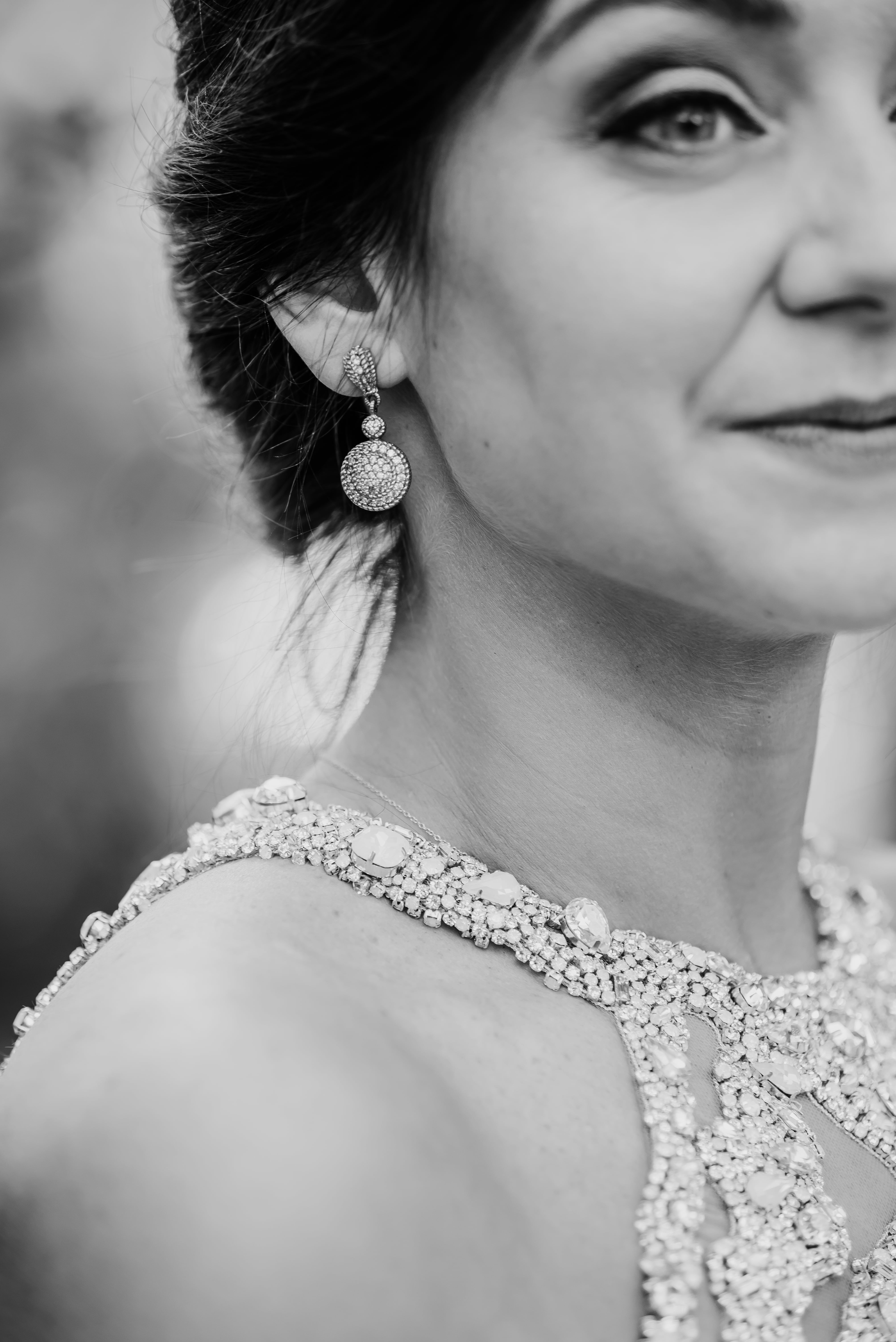 Detail shot of brides stunning hair and makeup done by Cali Stott Artistry as she stands in her Hayden Olivia gown captured by Shutter Owl Photography