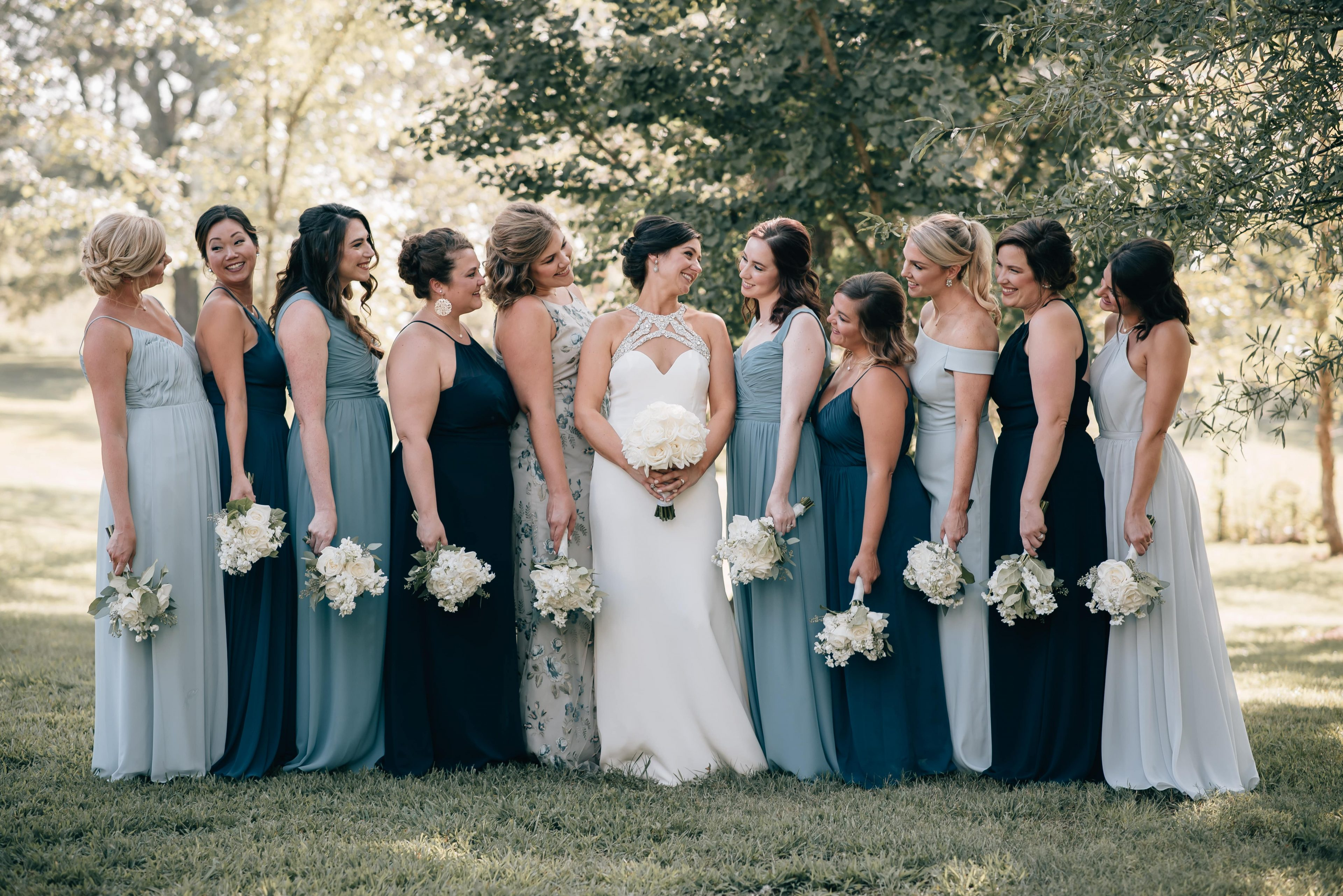 Bridesmaids were a variety of blue dresses from Brideside and pose with the bride wearing a simple white gown from Hayden Olivia Bridal