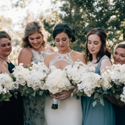 Bride and bridesmaids pose with white bouquets created by Party Blooms featuring simple white roses and greenery accents