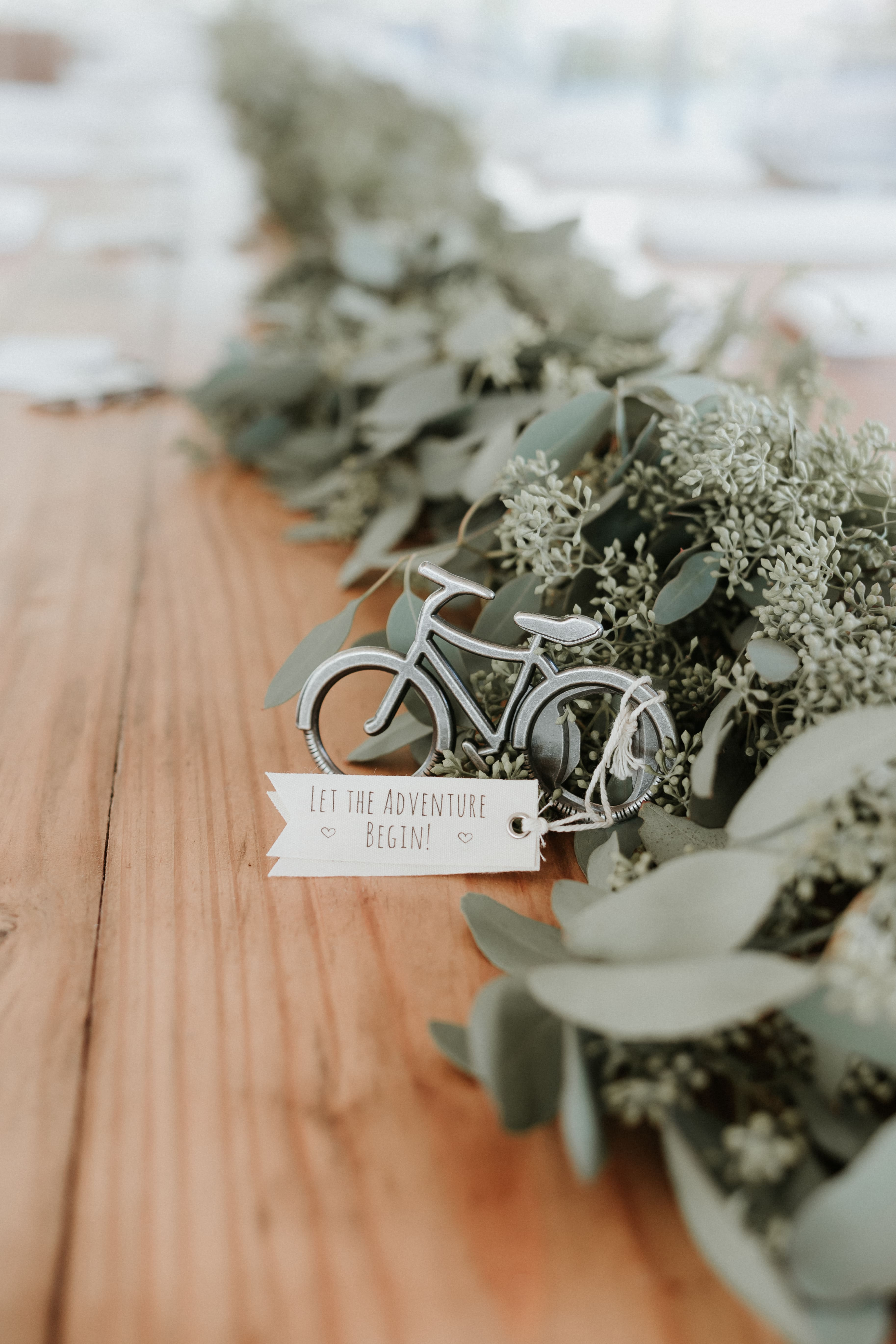 Greenery garland and fun bicycle bottle opener favor set the scene for a relaxed evening at The Ivy Place captured by Shutter Owl Photography