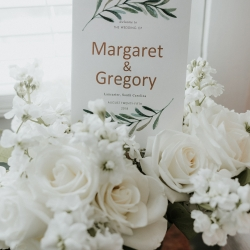 Graphics Matter created a simple wedding welcome sign with green accents placed among a simple white wedding bouquet created by Party Blooms