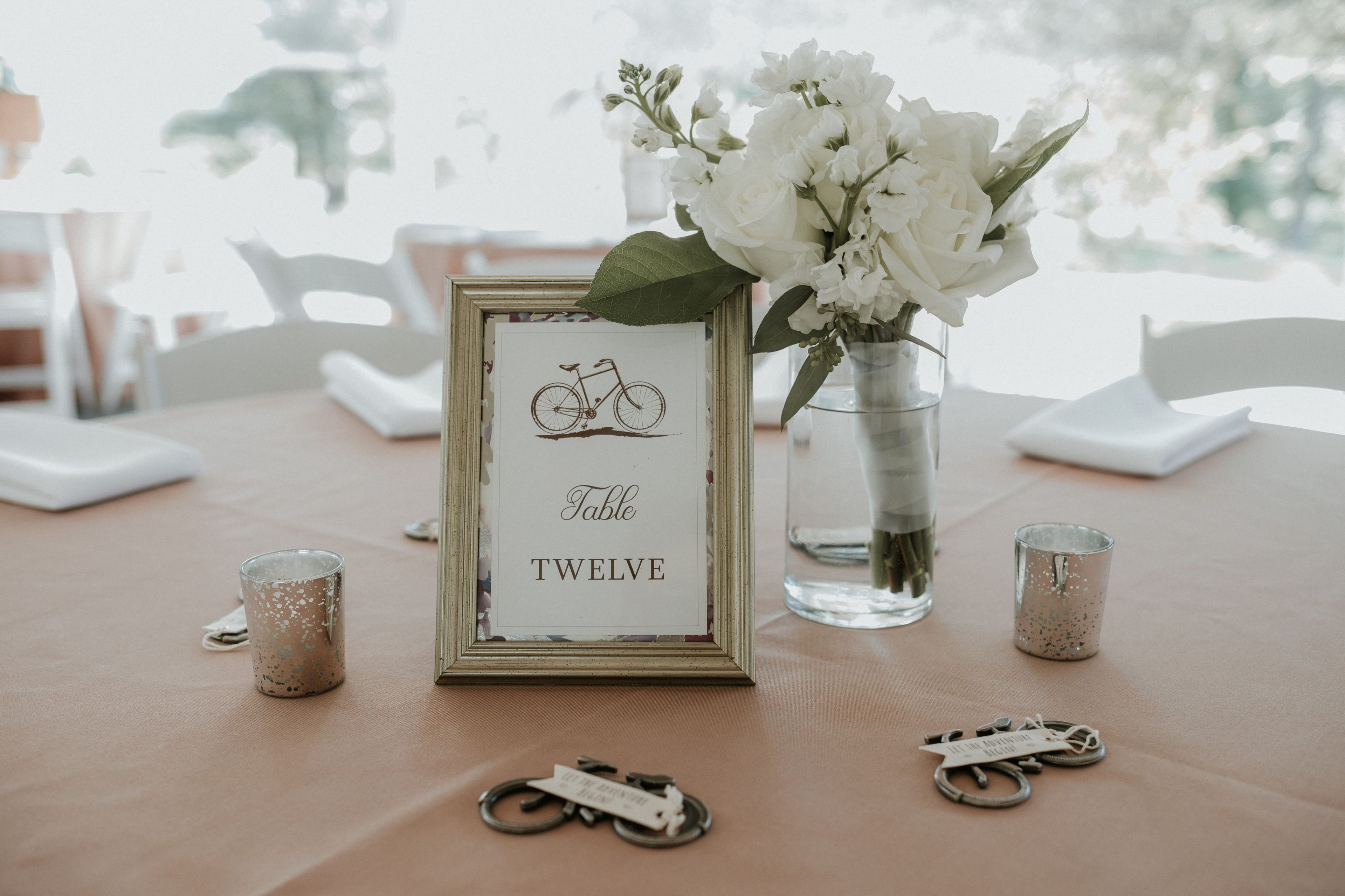 Bicycle themed wedding at The Ivy Place featured custom bicycle table numbers and bicycle bottle opener favors for guests all designed by Magnificent Moments Weddings