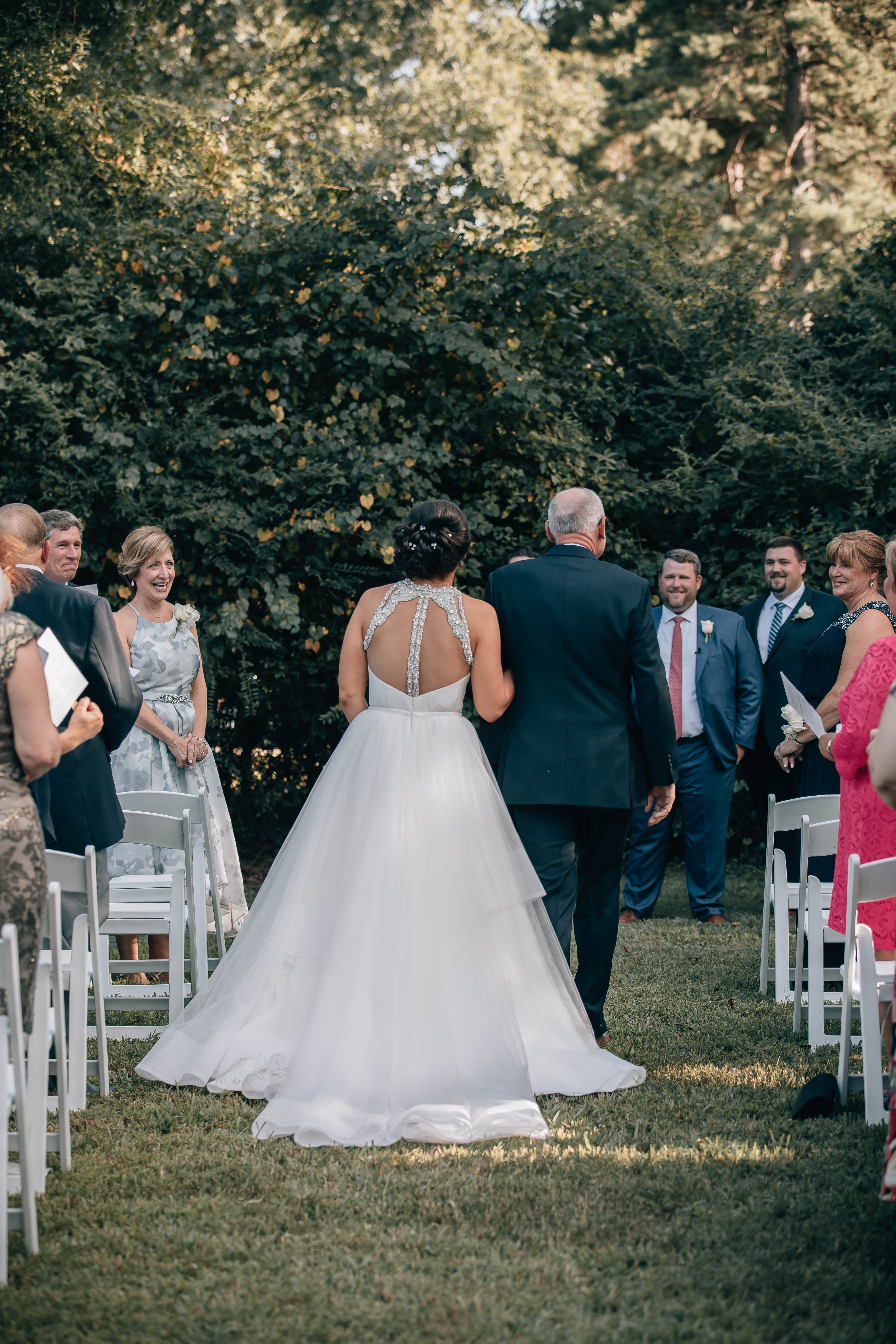 Bride is escorted down the aisle by her father to her ceremony at The Ivy Place designed and coordinated by Magnificent Moments Weddings