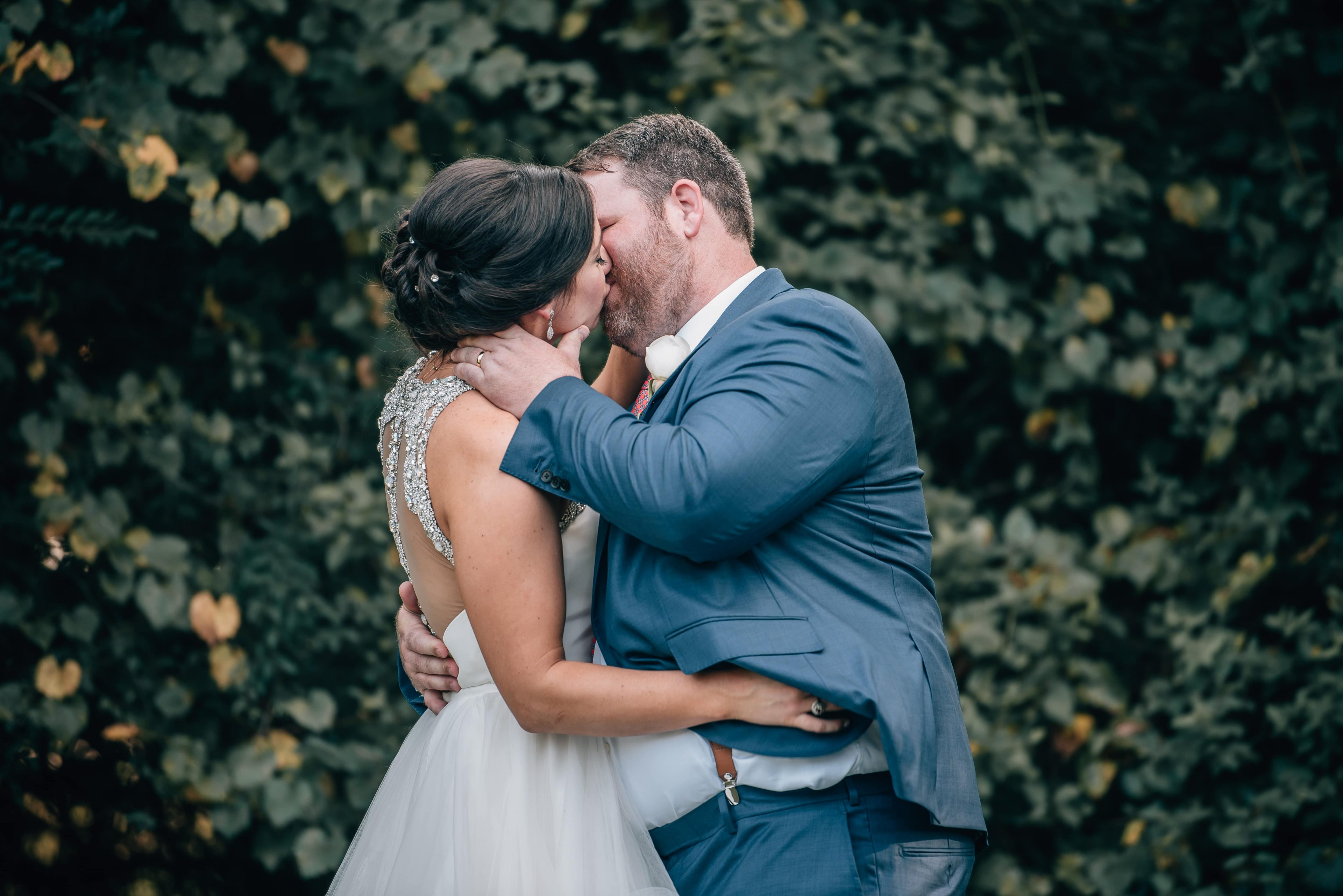 Bride wears a stunning dress by Hayden Olivia with gem details on the back as she kisses her groom during their summer wedding at The Ivy Place