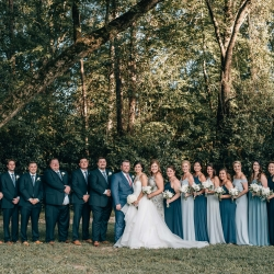 Bride and groom pose with their bridal party under an old oak tree at The Ivy Place captured by Shutter Owl Photography