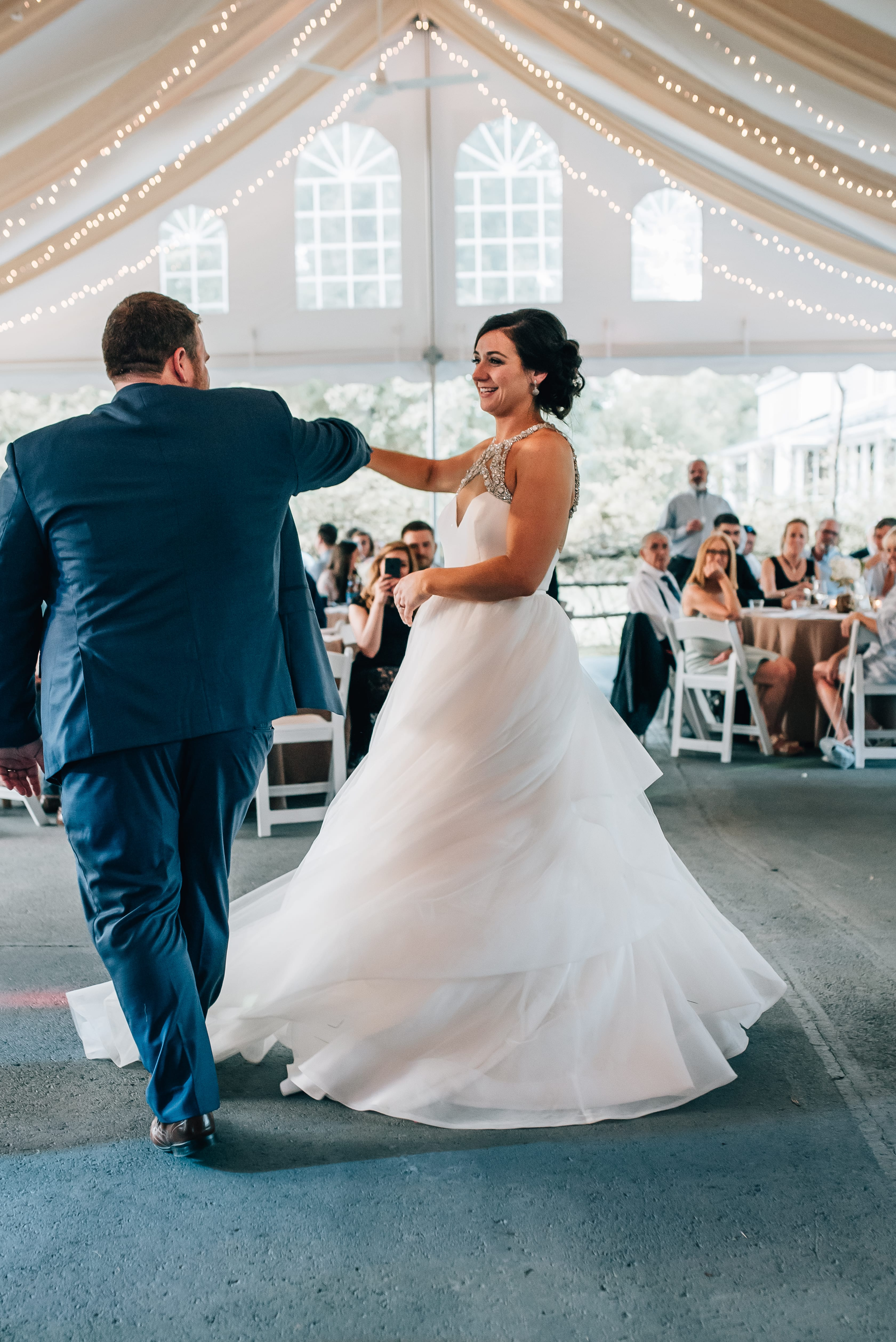 Groom spins his bride during their first dance at a sweet summer wedding designed by Magnificent Moments Weddings at The Ivy Place