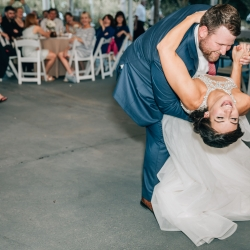 Bride and groom share a dip during their first dance to music by Southside Station at their fun summer wedding at The Ivy Place