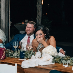 Bride enjoys hearing toast from her family at her Ivy Place wedding reception captured by Shutter Owl Photography