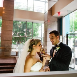 Groom feeds bride a sweet treat during their Uptown Charlotte wedding at The Ritz Carlton