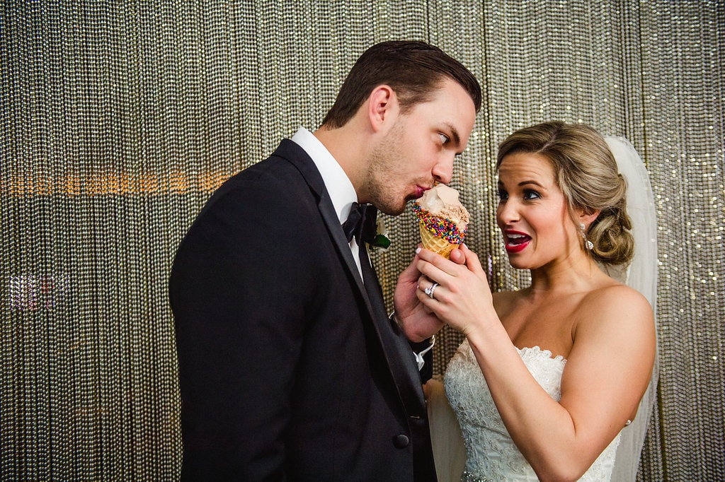 Bride feeds groom a sweet treat during their Uptown Charlotte wedding