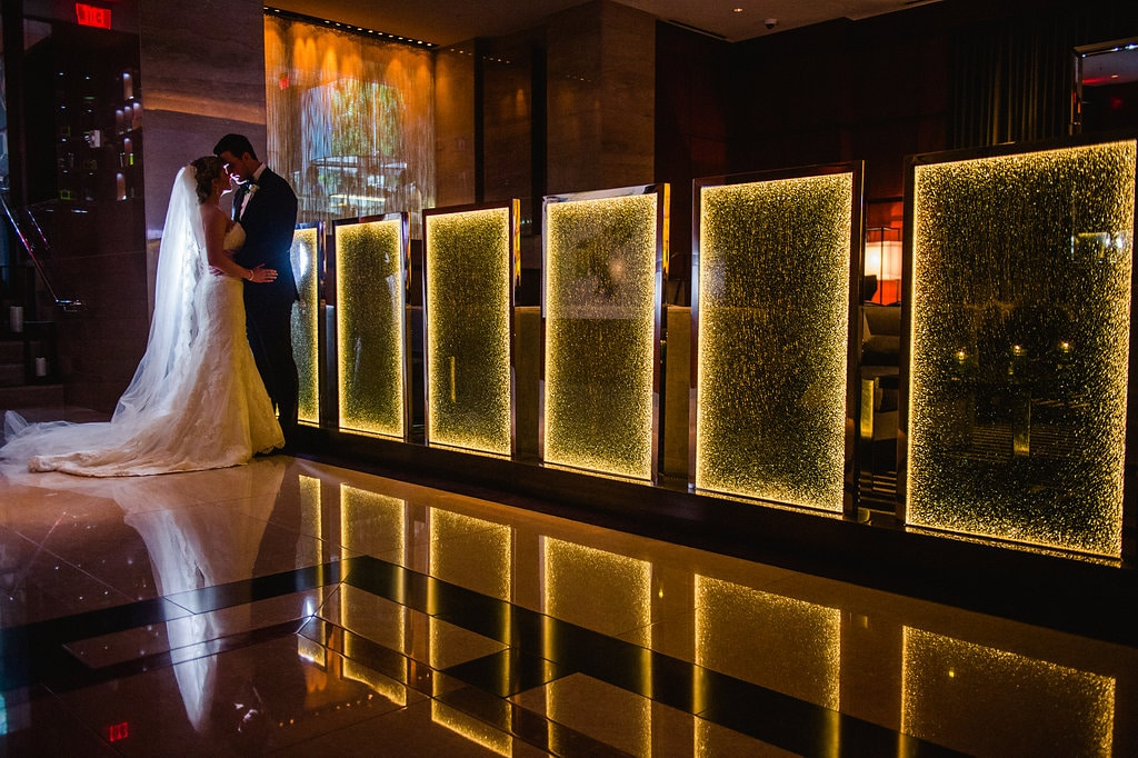 Bride and groom embrace during their Ritz Carlton reception captured by Smitten and Hooked