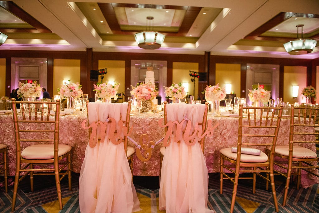 Bride and groom's chairs are designated with Mr and Mrs signs for a wedding reception at The Ritz Carlton