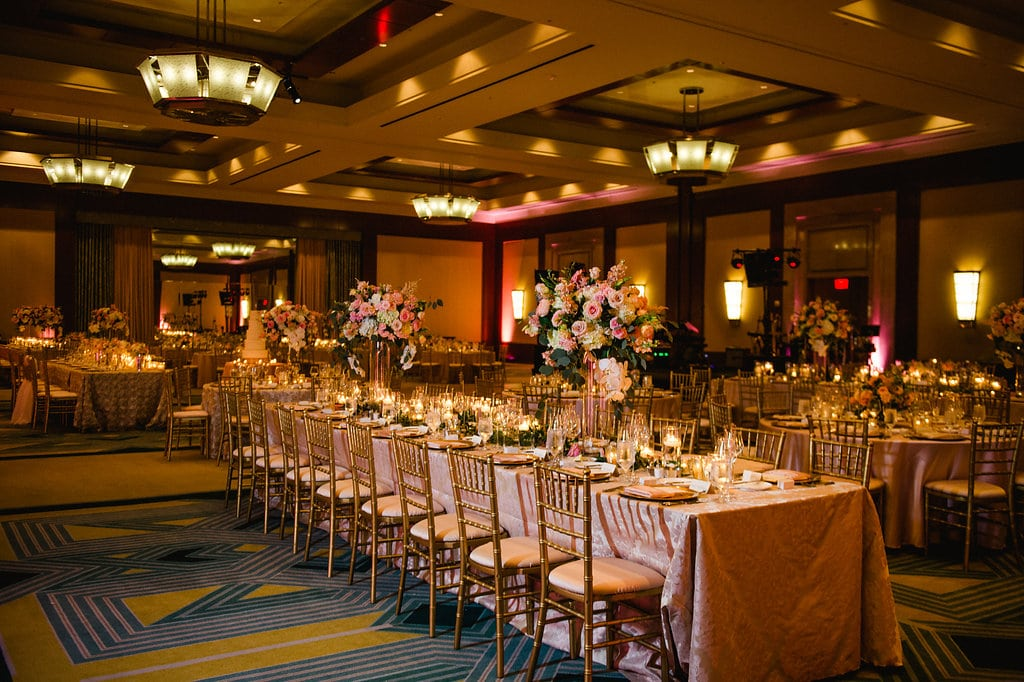 Ritz Carlton ballroom is set with blush pink linens and gold chivari chairs from Party Reflections for a stunning wedding reception captured by Smitten and Hooked