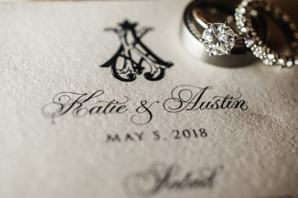 Smitten and Hooked capture a detail shot of a stunning wedding invitation and bridal rings for an Uptown Charlotte wedding