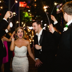 Bride and groom depart from their Ritz Carlton wedding through a sparkler send off coordinated by Magnificent Moments Weddings