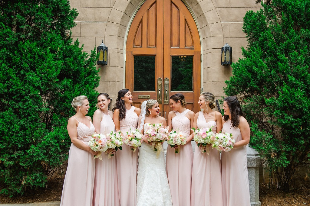 Bride and bridesmaids wearing soft pink dresses pose before the wedding ceremony at First Presbyterian Chruch
