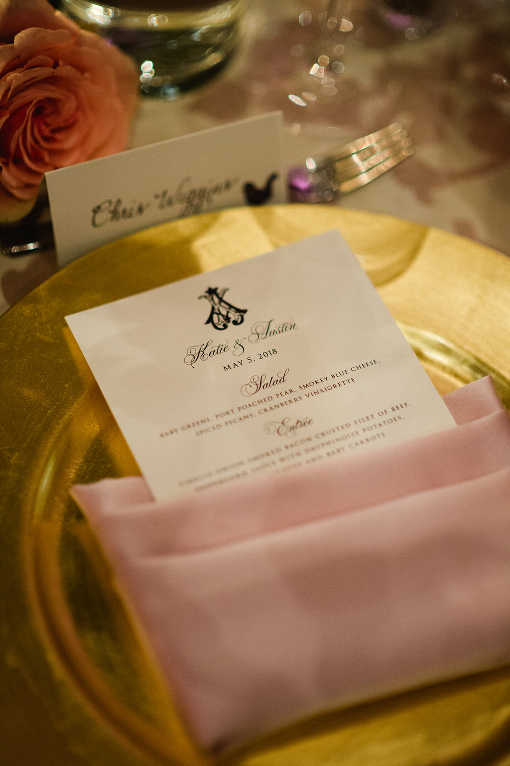 Smitten and Hooked capture a detail shot showing off a gold charger, pink napkin, and menu card for an Uptown Charlotte wedding coordinated by Magnificent Moments Weddings