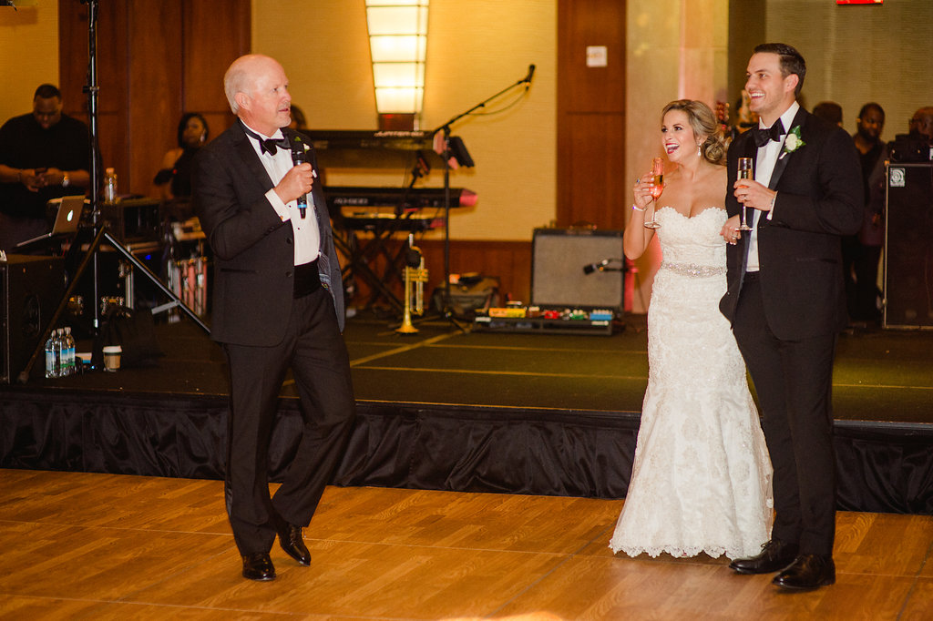 Bride and groom listen to a family toast during their uptown reception at The Ritz Carlton coordinated by Magnificent Moments Weddings