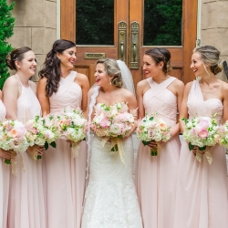 Smitten and Hooked capture a bride posing with her bridesmaids as they hold stunning bouquets designed by The Flower Diva