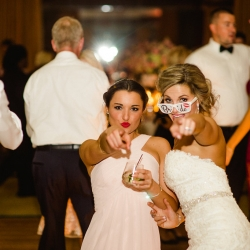 Bride and a bridesmaids pose for Smitten and Hooked during their wedding reception at The Ritz Carlton Uptown