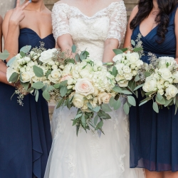 Bride shows off a stunning bridal bouquet featuring pink roses and white flowers
