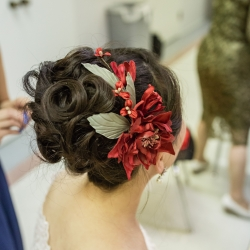 Bridal updo featured striking red flowers for her wedding ceremony coordinated by Magnificent Moments Weddings