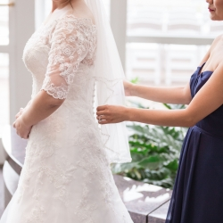 Bride gets dressed as she prepares for her wedding ceremony coordinated by Magnificent Moments Weddings
