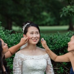 Bride shares a sweet moment with her bridesmaids as they take pictures before their wedding at The Mint Museum Randolph