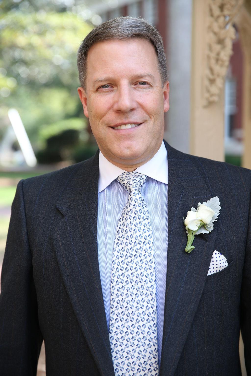 Groom prepares for her wedding at Belk Chapel wearing a dark suite and light blue shirt