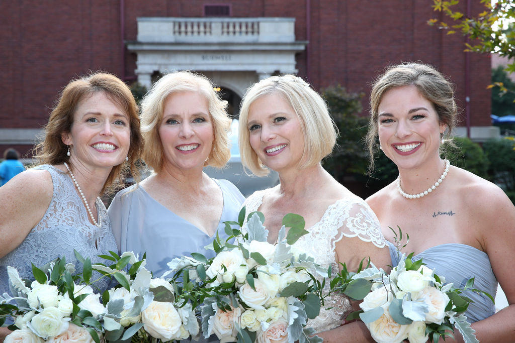 Bride poses with her bridesmaids wearing soft blue dress and holding beautiful bouquets of white accented by soft blue flowers created by Party Blooms
