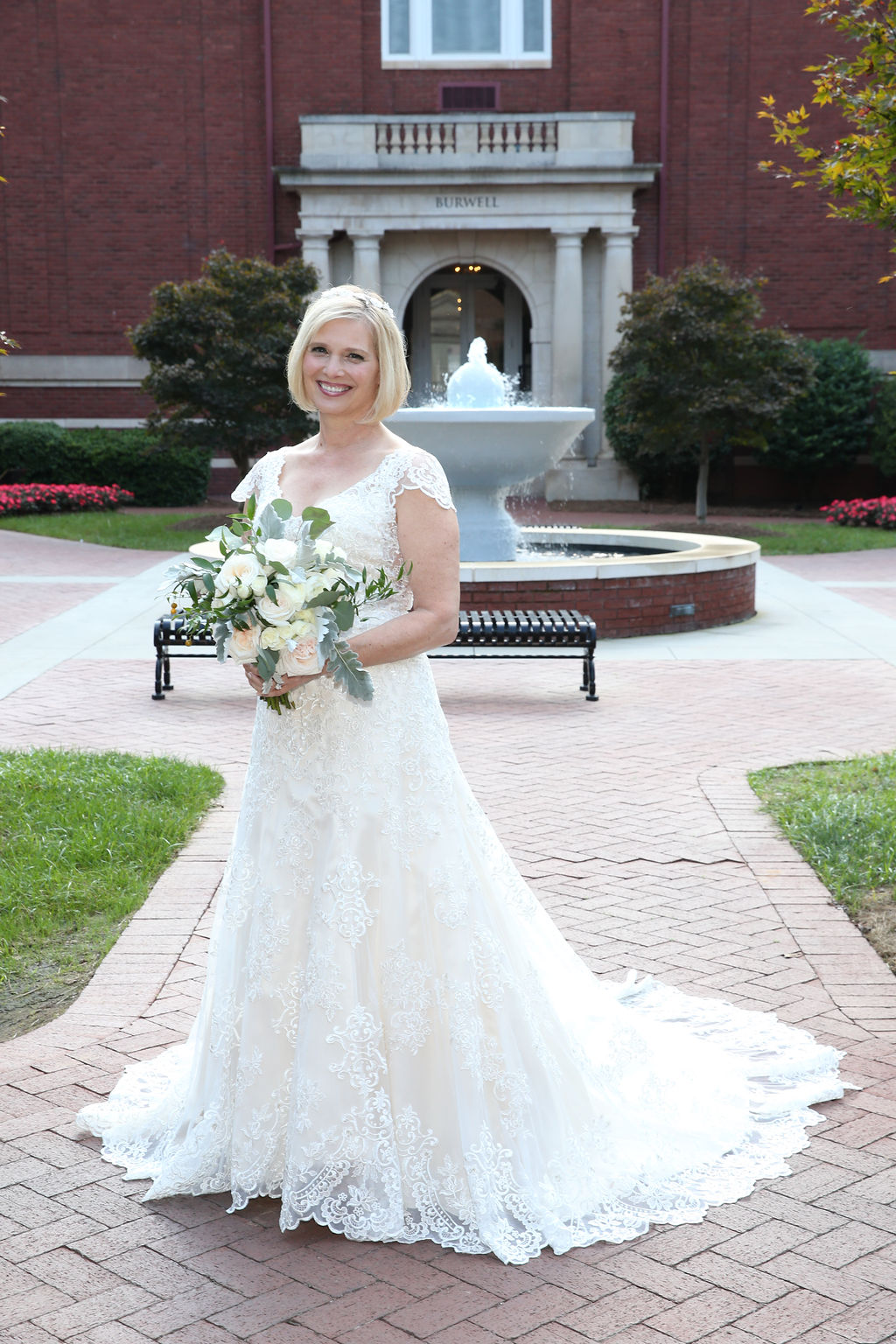 Bride poses on the grounds of Belk Chapel holding her bridal bouquet designed by Party Blooms