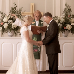 Stauss Studios captures bride and groom exchanging vows during their ceremony at Belk Chapel