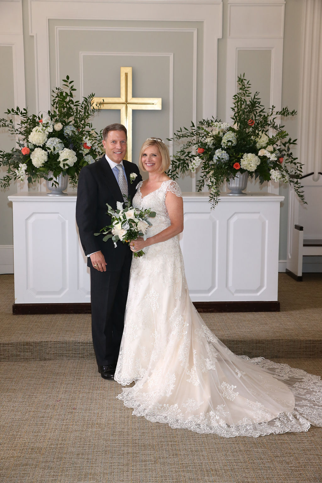 Bride and groom pose in front of the altar at Belk Chapel after exchanging their vows
