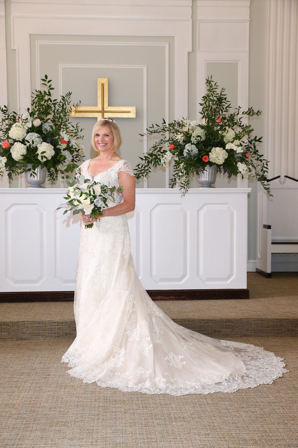 Bride poses with a delicate white bouquet created by Party Blooms for her wedding coordinated by Magnificent Moments Weddings
