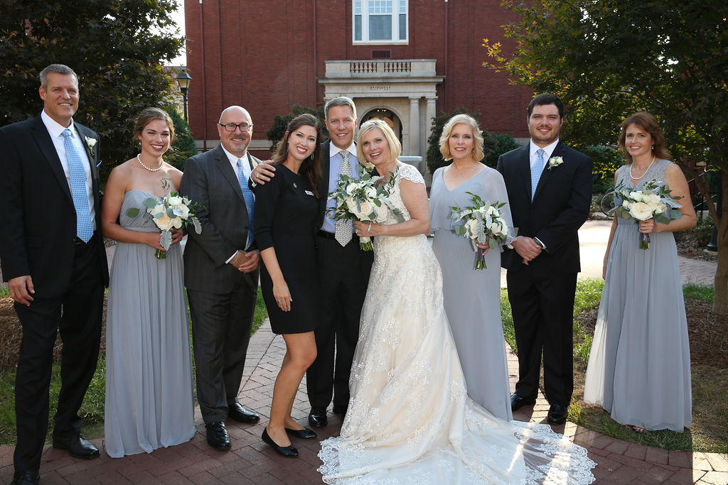 Bride and groom pose with wedding coordinator Amanda after their ceremony at Belk Chapel