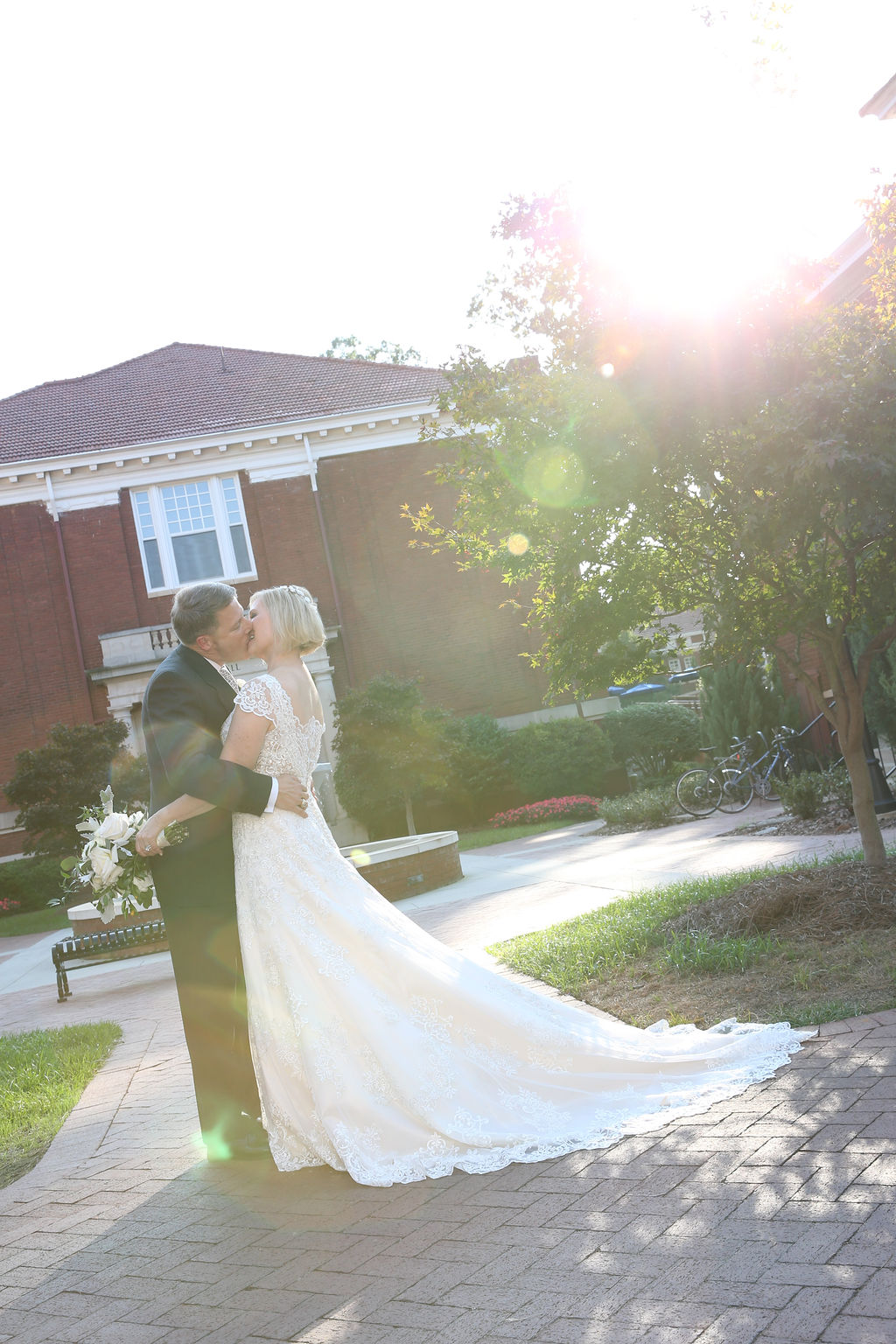 Bride and groom share a kiss after their wedding ceremony at Belk Chapel captured by Strauss Studios