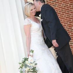 Bride and groom pose in front of Belk Chapel after their wedding ceremony coordinated by Magnificent Moments Weddings
