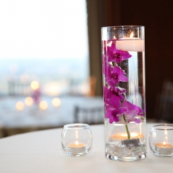 Simple centerpieces of floating candles creates a romantic setting for a wedding at Charlotte City Club