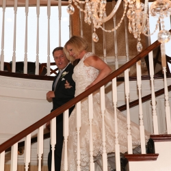 Bride and groom enter into their Charlotte City Club reception down an elegant stairwell captured by Strauss Studios