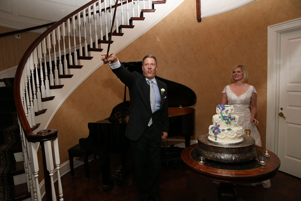 Groom shows off his sword used for a unique cake cutting at their Charlotte City Club reception