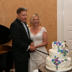 Bride and groom cut their cake created by Publix during their wedding reception captured by Strauss Studios