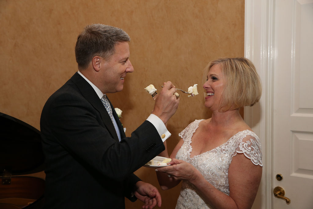 Bride and groom exchange cake during their wedding reception coordinated by Magnificent Moments Weddings