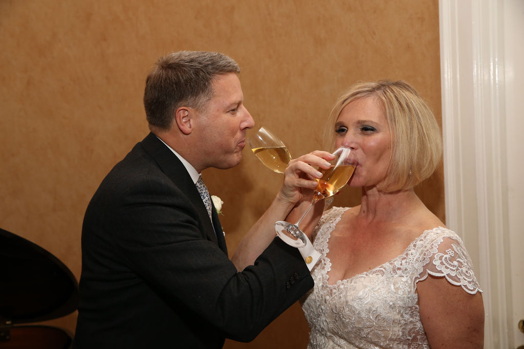 Bride and groom share a champagne toast during their wedding reception coordinated by Magnificent Moments Weddings
