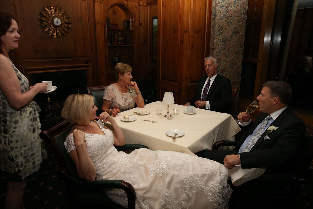 Bride and groom relax with friends and family during their Charlotte City Club wedding
