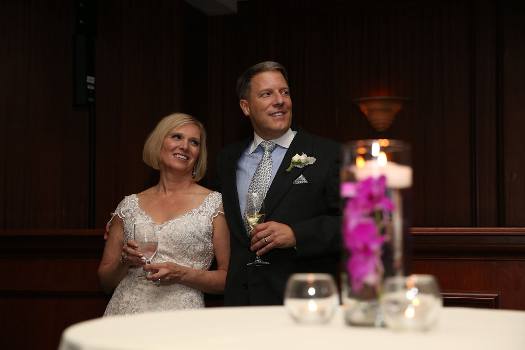 Bride and groom smile as their family toast their marriage during their wedding reception captured by Strauss Studios