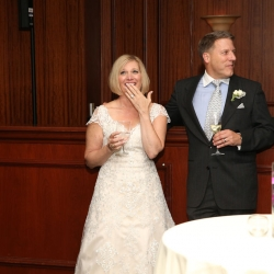 Bride smiles during toasts at her Charlotte City Club wedding