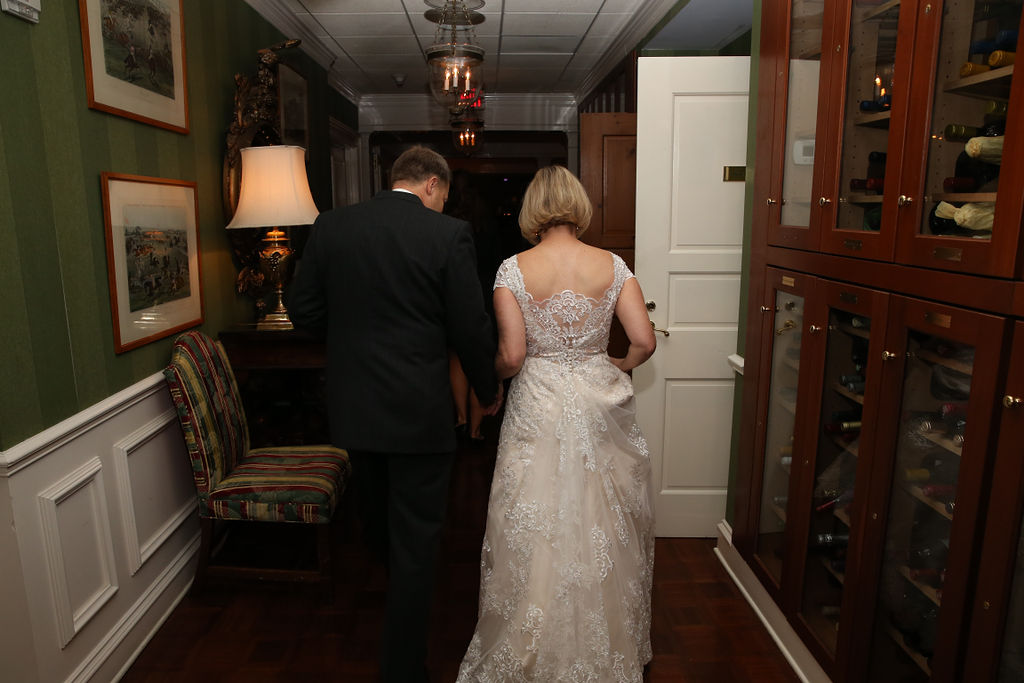 Bride shows off the lace back detail of her gown from J Majors Boutique during her wedding coordinated by Magnificent Moments Weddings